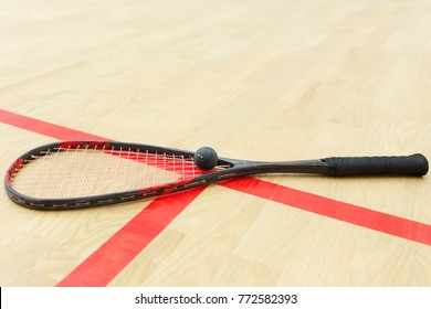 squash racket and ball on the wooden floor. Photo with selective focus