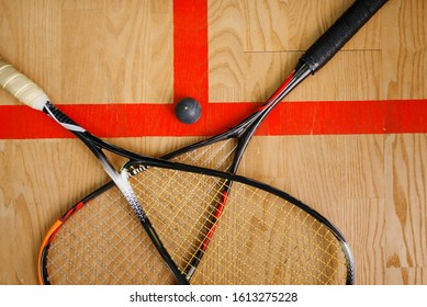 Squash rackets and ball on court floor, top view