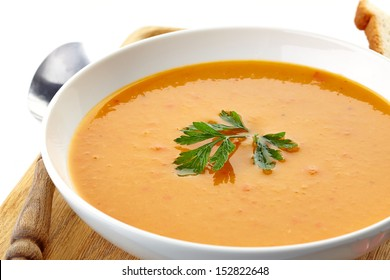 squash soup and parsley leaf in a white plate
