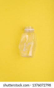 Squashed plastic bottle on yellow background. Plastic utilisation concept. Ecological problem, global environment.