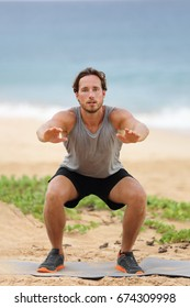 Squat exercise fitness man training squats for glutes and quadriceps muscles doing workout burpees working out beach in summer outdoors.