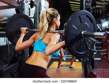 Squat woman with barbell