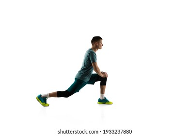 Squats. Young caucasian male model in action, motion isolated on white background with copyspace. Concept of sport, movement, energy and dynamic, healthy lifestyle. Training, practicing. Authentic.