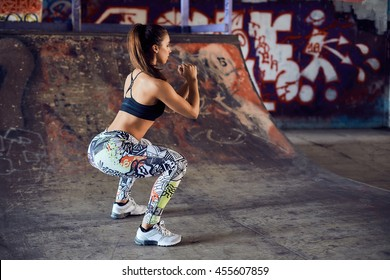 Squatting muscular woman on the urban city background. fitness, sport, exercising and healthy lifestyle concept - woman doing squats outdoors.