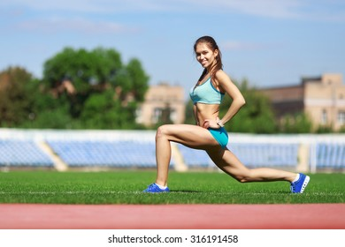 squatting.warming-up.young beauty girl do exercises at the stadium