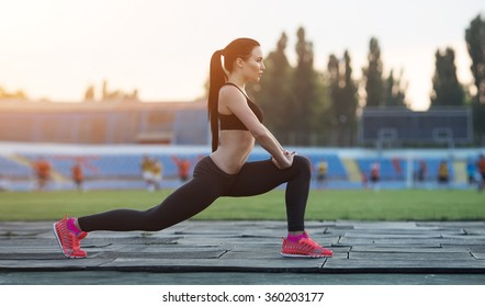 squatting.young beauty girl do exercises at the stadium