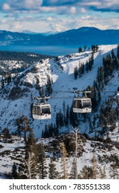 Squaw Valley, California - December 20, 2017: Two gondolas pass each other, at the Squaw Valley Ski Resort, in the Sierra Nevada Mountains of California, with Lake Tahoe in the background.