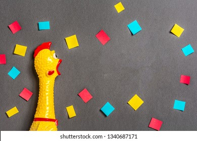 Squawking chicken or squeaky toy shouting on dark background with confetti. Concepto of back to school, education or learning