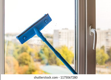 Squeegee glides over the glass indoors, making it clean. Window cleaning service concept.