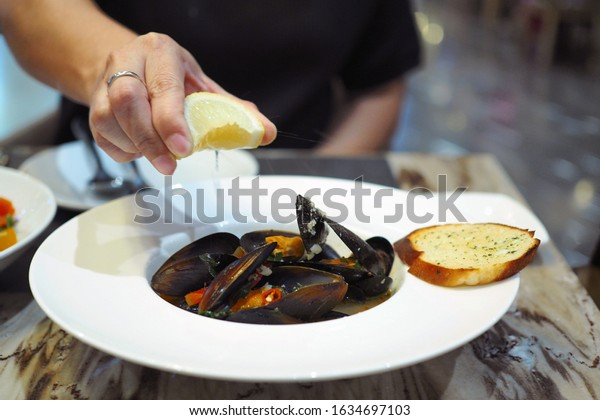 Squeeze slice of lemon over plate of Spicy Blue Mussel sauteed with white wine. Selective focus.