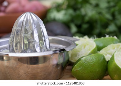 Squeezed lime halves with metal manual juicer
