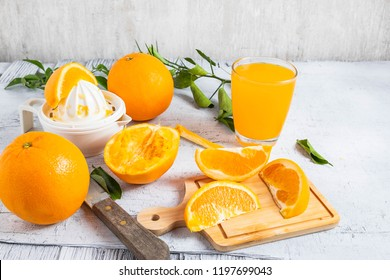 Squeezed orange juice and fresh oranges fruits on white wooden table