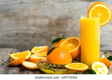Squeezed orange juice and fresh oranges fruits on rustic wooden table