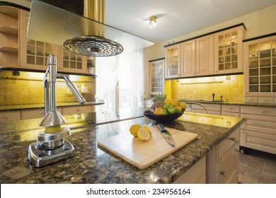 Squeezer on granitic countertop in modern kitchen