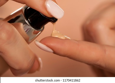 squeezing liquid foundation from the pump to the finger