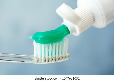 Squeezing toothpaste on brush against color background, closeup