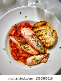 Squid with tomatoes and grilled bread plate Italian comfort food.