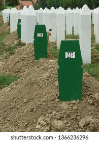 Srebrenica / Bosnia and Herzegovina - July 30 2013: Anonymous graves of Muslim victimes from 1995 in Srebrenica, green wooden tombstones with numbers, white decorative marble on traditional shape
