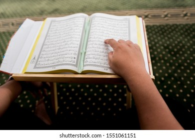 Sri Kembangan,Selangor - OCT 2019 :  al-Quran is a holy book of Islamic guidance isolated. religion concept. An open page of Quran on wooden stand above prayer mat open page of Quran on wooden stand
