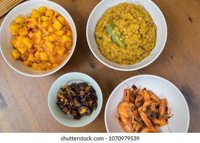 Sri Lanka Curry with prawns, pineapple, lentils and aubergine served in white bowls on wooden background
