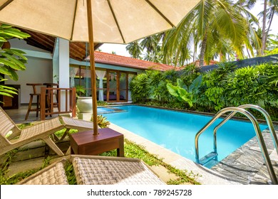Sri Lanka - November 4, 2017: Villa with pool in a tropical hotel. Beautiful swimming pool with blue water. Luxury tropical place to relax.