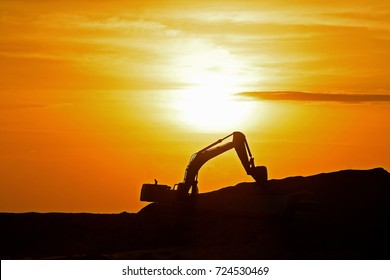 Sri Lanka - October 2, 2016: It is already dusk on a Sunday, and an excavator is still at work in a land reclamation site in new Colombo port city.