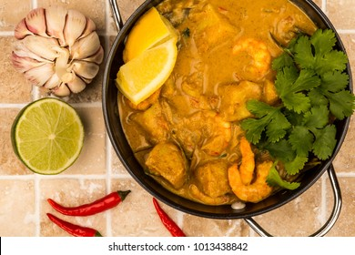 Sri Lanka Style King Prawn Curry With Lemon and Coriander Herbs On A Tiled Kitchen Worktop Counter or Tabletop