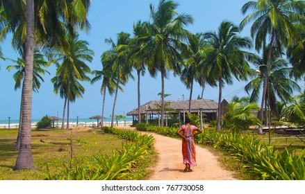 Sri lanka woman in beautiful sari walking toward beautiful Nilaveli beach