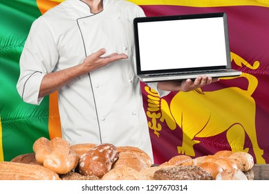 Sri Lankan Baker holding laptop on Sri Lanka flag and breads background. Chef wearing uniform pointing blank screen for copy space.