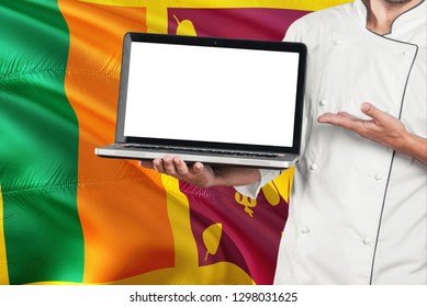 Sri Lankan Chef holding laptop with blank screen on Sri Lanka flag background. Cook wearing uniform and pointing laptop for copy space.