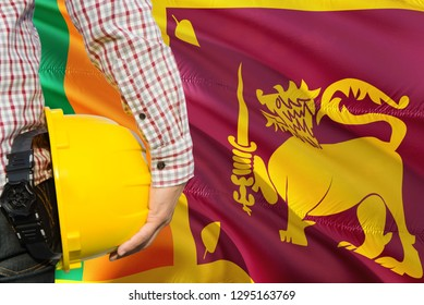 Sri Lankan Engineer is holding yellow safety helmet with waving Sri Lanka flag background. Construction and building concept.