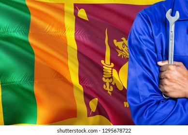 Sri Lankan Mechanic in blue uniform is holding wrench against waving Sri Lanka flag background. Crossed arms technician.