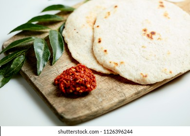 Sri Lankan Pol Roti and katta sambol on rustic wood with curry leaf on white background