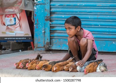 SRIMANGAL, BANGLADESH - 13 APRIL, 2018: A boy looks after chickens for sale on a sidewalk of a street in an Asian city.