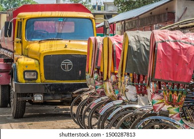 SRIMANGAL, BANGLADESH - 13 APRIL, 2018: A truck stands at the end of a row of cycle rickshaws in an Asian city.