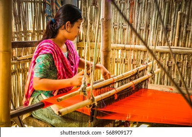 Srimongal, Bangladesh - circa July 2012: Young black-haired woman with pink scarf sits in shelter and weaves on simple wooden loom in Srimongal, Bangladesh. Documentary editorial.