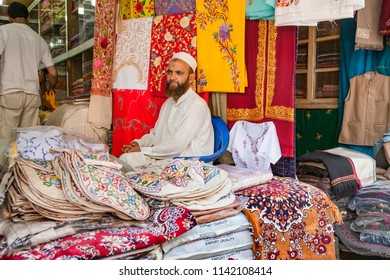 Srinagar ,23 June,2008:Portrait of   muslim shop keeper in white clothes, with beard and cap,sitting in ready made cloth shop  against  colorful embroidery textiles background, Jammu and Kashmir,India