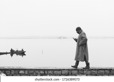 Srinagar, India- 25th Feb 2020- A monochromatic image of a man wearing Phiran (Winter clothing) looking for mobile network with Dal Lake behind him