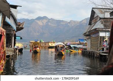 Srinagar, India - February 2018 : Shikara (traditional Kashmiri boat) on floating village in Dal Lake.