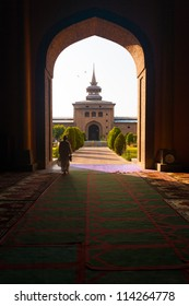 Srinagar, India - July 11, 2009: Muslim man walks through a large open arch doorway leading to the Main Mosque, Jama Masjid, courtyard in Kashmir