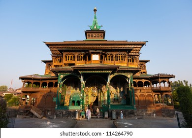 Srinagar, India - July 15, 2009: Muslim women enter the front facade entrance the uniquely wooden Shah E Hamdan mosque for morning prayers on a clear sunny, blue sky day