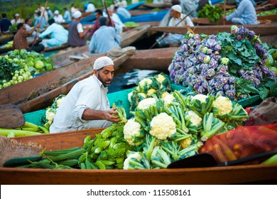 Srinagar, India - July 17, 2009: Kashmiri man transfers vegetables from his shikara boat among many other sellers at the daily floating market on Dal Lake in Kashmir