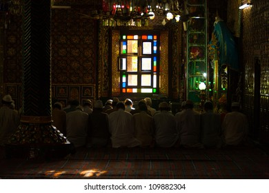 Srinagar, India - July 22, 2009: Muslim men kneeling on floor while praying in rows inside the ornate famous Shah E Hamdan mosque