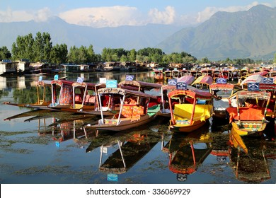 SRINAGAR, INDIA - JULY 29, 2015: Small wooden boats are called Shikara, that local people and tourist use for traveling and transportation in Dal lake, Srinagar, Jammu & Kashmir. JULY 29 2015