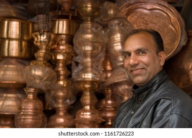 SRINAGAR, INDIA - MAY 5 2009: Unidentified vendor sells copper utensils in his store in Srinagar, Kashmir, India. Traditional crafts are well preserved and popular in Kashmir since ancient times.