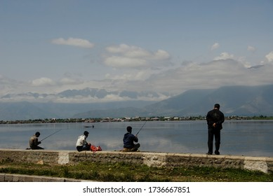 SRINAGAR, INDIA - MAY 6 2009: Unidentified men go fishing in The Dal Lake, Srinagar, Kashmir, India. For most of local dwellers fishing with a rod is not a source of livelihood, just a hobby.