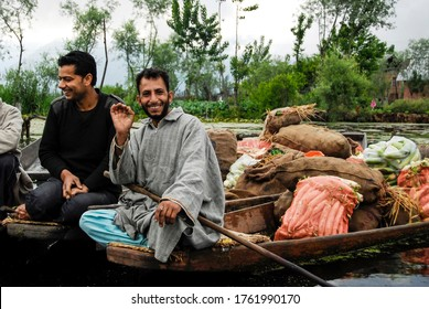 SRINAGAR, INDIA - MAY 6 2009: Unidentified men sell vegetables at floating market on The Dal Lake in Srinagar, Kashmir, India. Floating market on The Dal Lake plays significant role for local people.