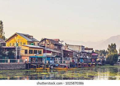 SRINAGAR, INDIA - October 2017: Dal lake at sunset time. Shikara boats on the water at Dal lake in the evening, Srinagar, Jammu and Kashmir, India