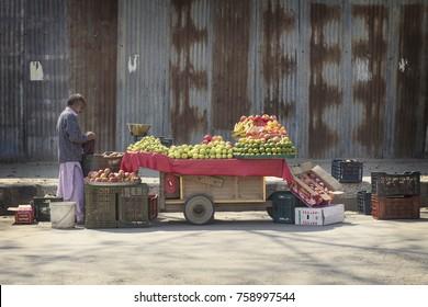 SRINAGAR, INDIA - October 2017: Indian fruit market. Indian man selling fruit on the street of old town Srinagar, Jammu and Kashmir, India