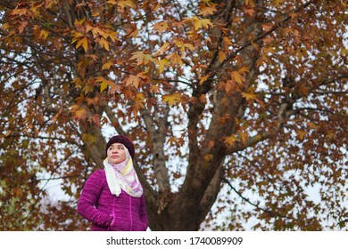 Srinagar, India -  September 27, 2017: Young Muslim Woman enjoying the warm autumn sun in the park. Sunny day in Srinagar, natural light, street photography. Portrait of a young woman in the park